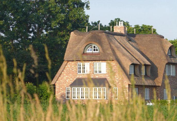 Sie blicken auf die Westseite des Hauses. Durch die großen Erkerfenster haben Sie einen Weitblick über Wiesen und Felder