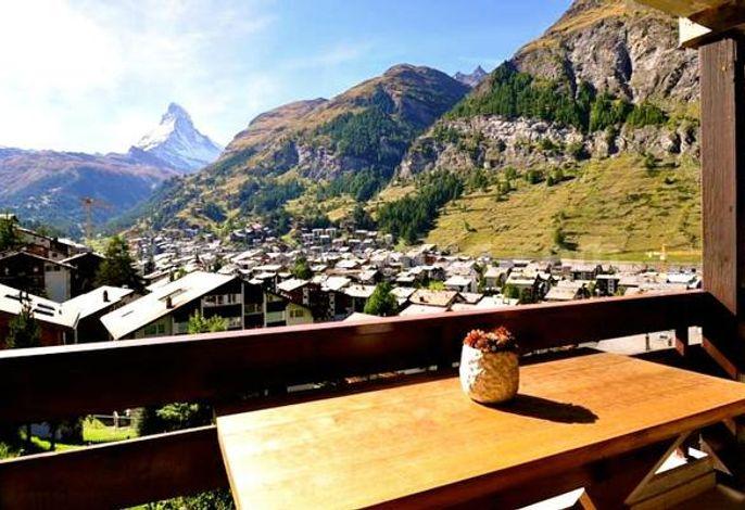 Sonniger Balkon mit Blick auf das Dorf und das Matterhorn. Liegestühle und Esstisch vorhanden.