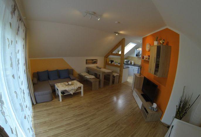 Wohnzimmer mit Blick auf die gemütliche Eckcouch und Esstisch