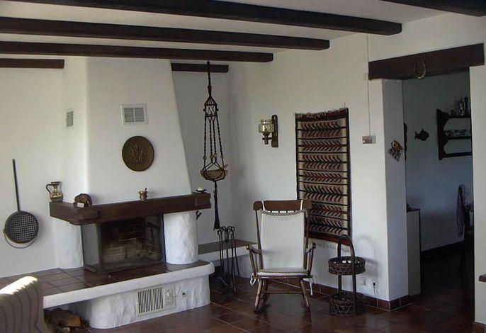 Wohnzimmer mit Cheminée und Schaukelstuhl für gemütliche Tessiner Stunden