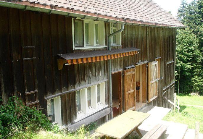 Vor der Hütte ist ein Esstisch.