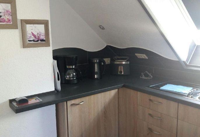 gemütliche Einbauküche mit Kaffeemaschine, Toaster, Wasserkocher und Herd mit vier Platten sowie Einbaukühlschrank