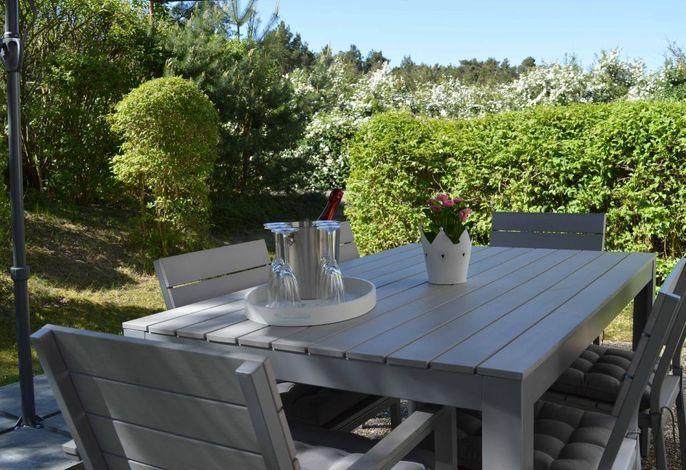 Sonnenterrasse im Garten mit großem Sonnenschirm und sechs Sitzplätzen.