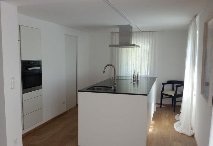Moderne und hochwertige Küche mit einer großzügigen Kochinsel und Küchenutensilien ausgestattet.