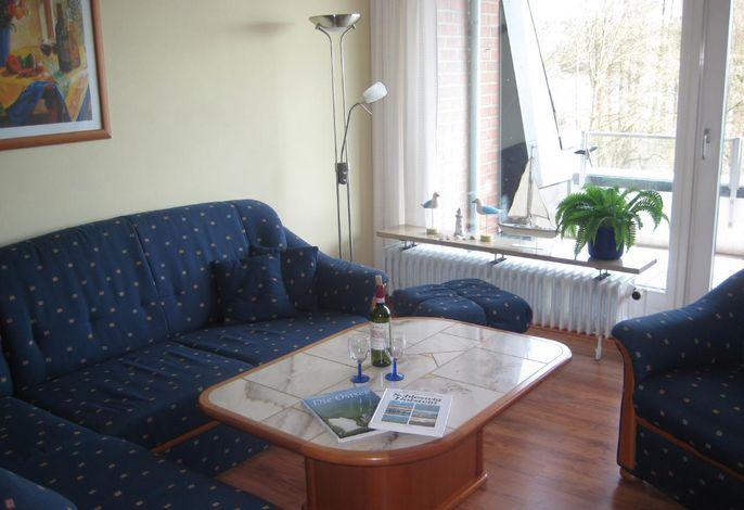 Wohnzimmer mit Couchecke und Balkon zur Wasserseite