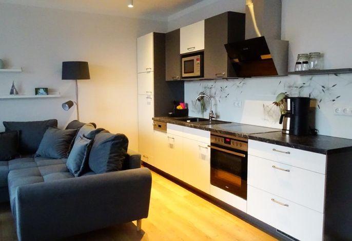 Gemütlicher Wohnraum mit integrierter Einbauküche