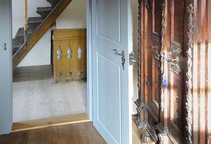 Blick vom Wohnzimmer in Richtung Flur mit der historischen Blockstufentreppe ins DG