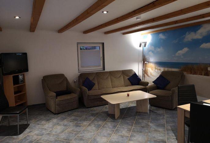 Wohnzimmer mit Essecke, abgeteilter Küche und Ausgang zur Terrasse
