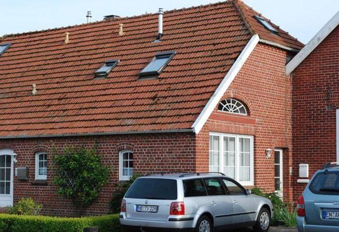 Die Wohnung (oben) von außen, anliegend die Parkplätze