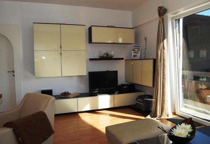 Wohnzimmer mit integriertem Doppelbett in dem Ledersofa sowie Essbereich mit Lederessecke und Tisch für 6 Personen