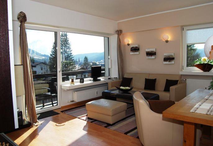 Wohnzimmer mit Lederessecke, Tisch und Seessel für 6 Personen