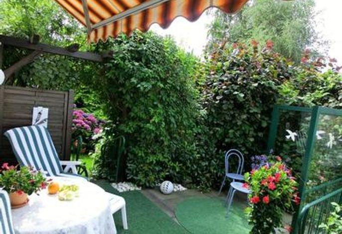 Dieselbe Terrasse, bestuhlt mit Liegesesseln (nach Wunsch)###br###3 Stufen (beidseitig Geländer) führen in den Garten.
