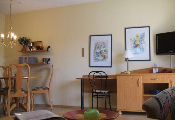 Wohnbereich mit Fernseher und Essecke