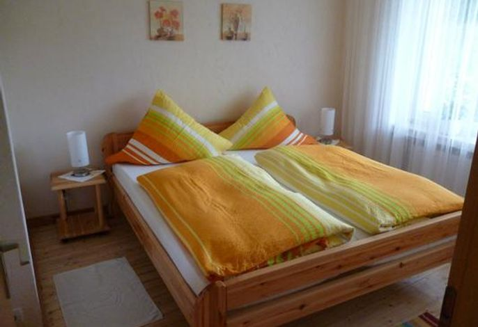 Schlafzimmer mit Doppelbett und zustellbarem Kinderbett