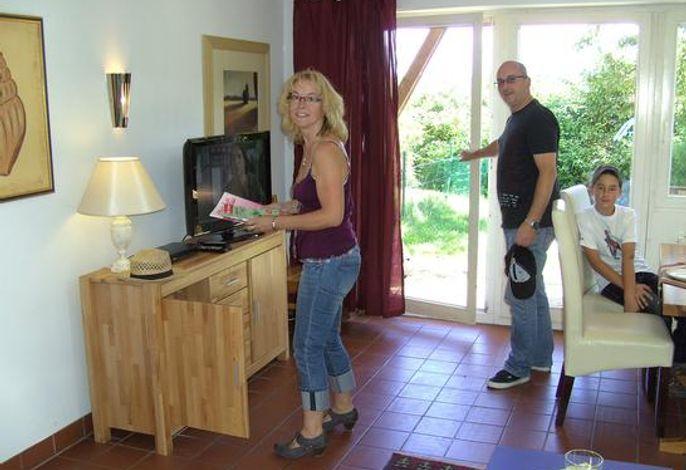 Wohnraum mit Sat-TV und Blick zur Terrasse