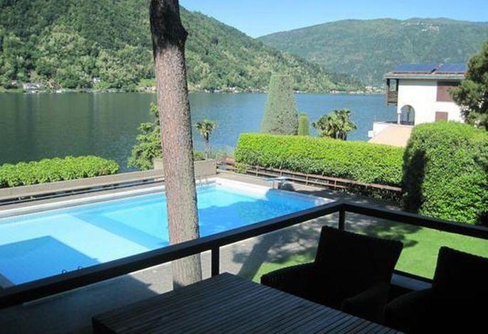 Blick vom Balkon über den großen Pool zum See