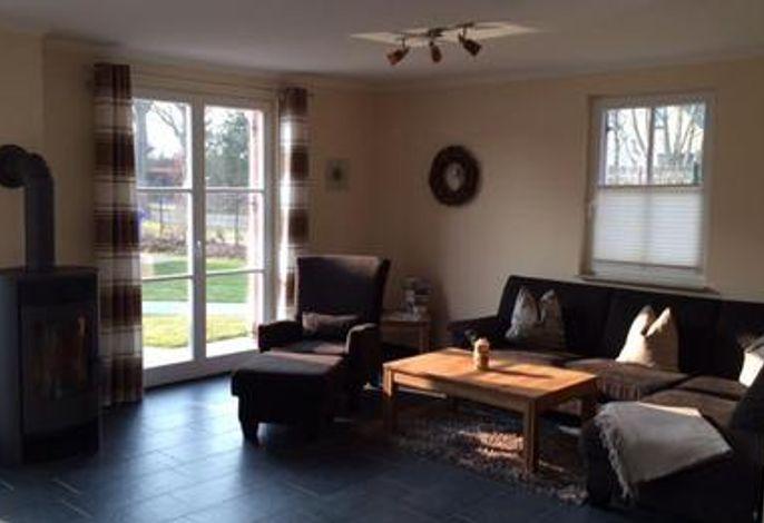 Wohnzimmer mit gemütlicher Couchecke und Kamin