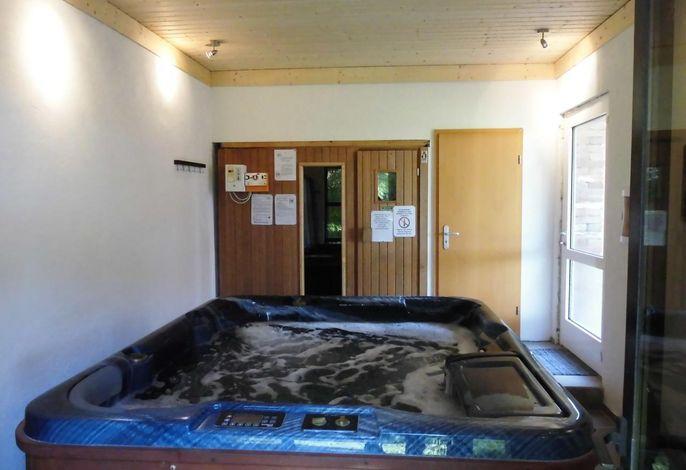Whirlpool und im Hintergrund die Sauna im Badehaus. Kann von Gästen aus Haus 1 und 2 genutzt werden