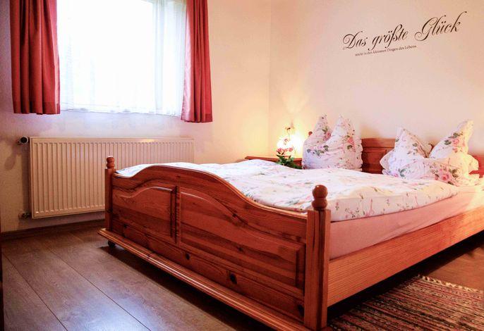 Das helle Schlafzimmer mit Doppelbett bietet Raum zum Erholen