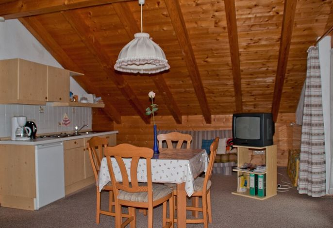Wohnraum mit Küchenzeile und Sitzgruppe