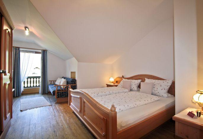 Schlafzimmer mit Schlafcouch und Balkon