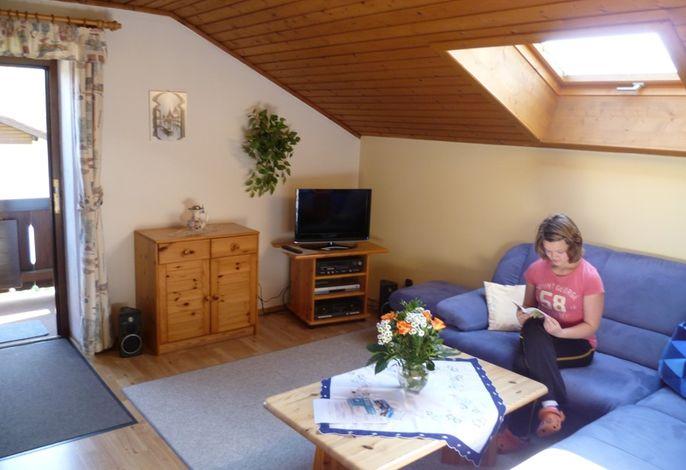 freundlich eingerichtetes Wohnzimmer mit Flat-TV