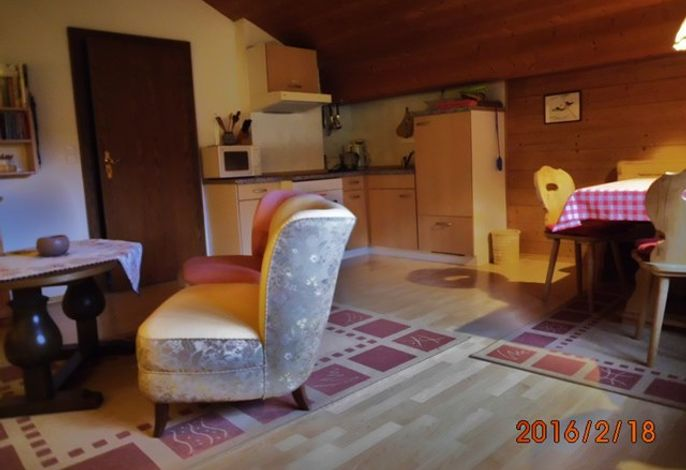 Gemütliches Wohnzimmer mit Eckbank und gut ausgestatteter Kochnische