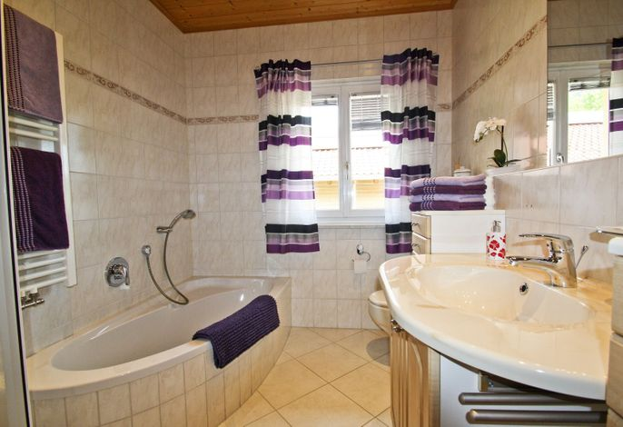 das Bad mit Badewanne und Dusche