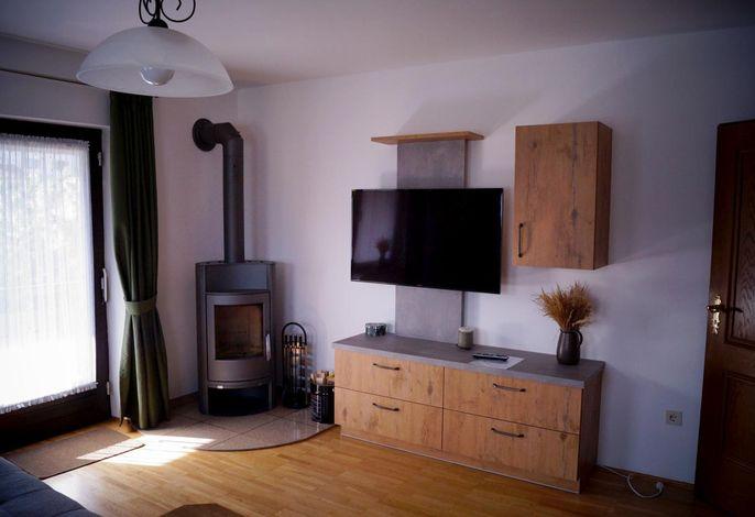 Das gemütliche Wohnzimmer mit Schwedenofen und Flachbildfernseher
