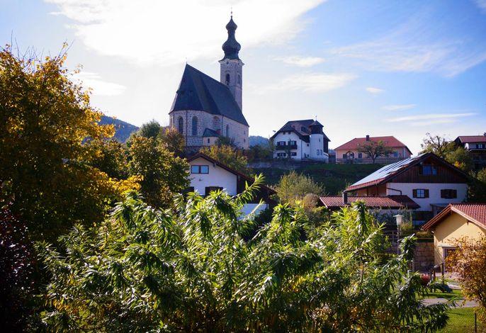 Der Blick vom Balkon zeigt zur Pfarrkirche Maria Himmelfahrt am nahe gelegenen Dorfplatz