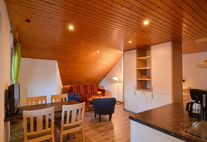 Wohnraum mit abgetrenntem Doppelbett und Küchenzeile