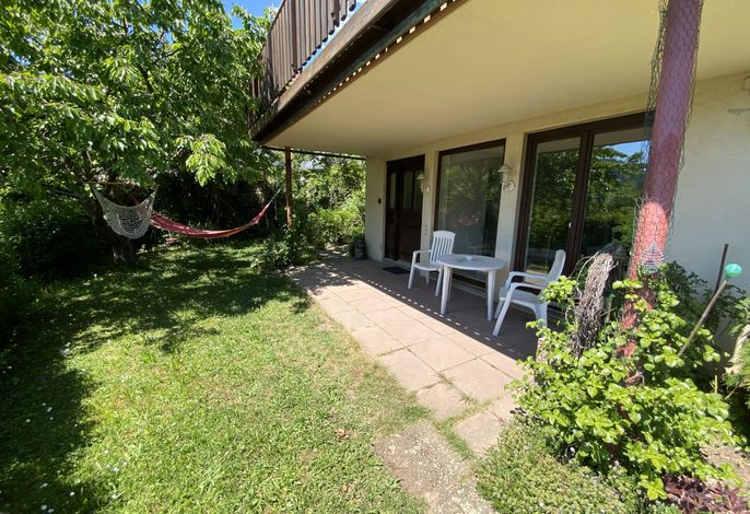 Überdachte Terasse mit direktem Gartenzugang vor der Ferienwohnung.
