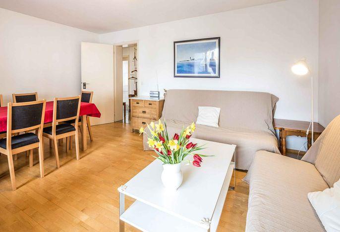 Wohnzimmer mit Esstisch und zwei aufklappbaren Schlafsofas