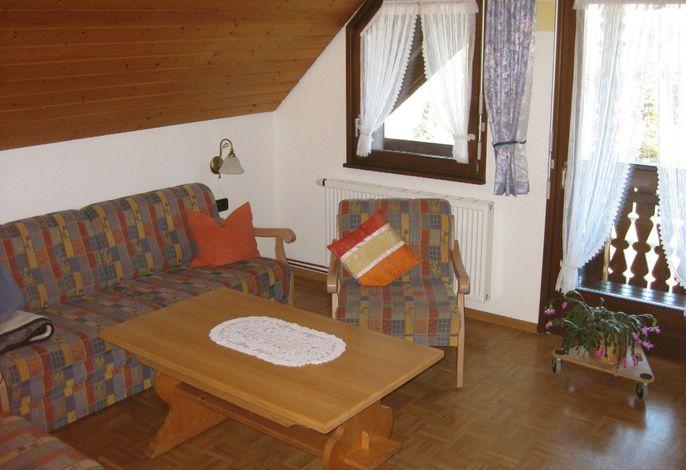 Wohnzimmer mit Sitzecke und Ausgang zum Balkon