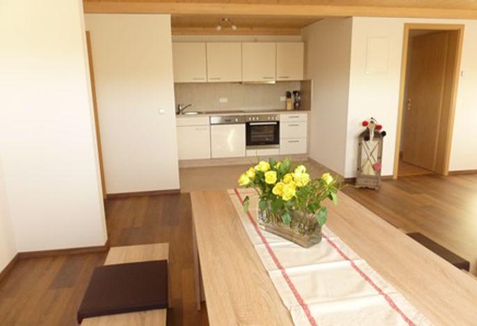 Esstisch mit Blick auf Küchenzeile und Garderobenraum