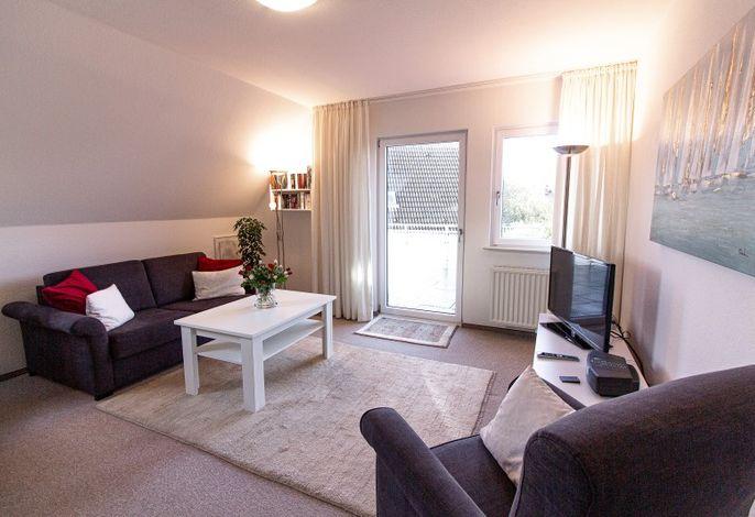 Wohnraum mit Essbereich und offener Küche mit Blick zum Balkon