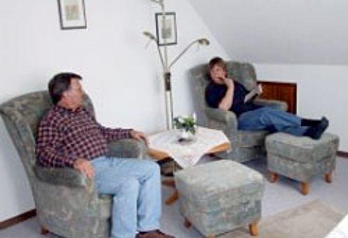 Der Wohnraum mit Ohrensesseln und Fußhocker