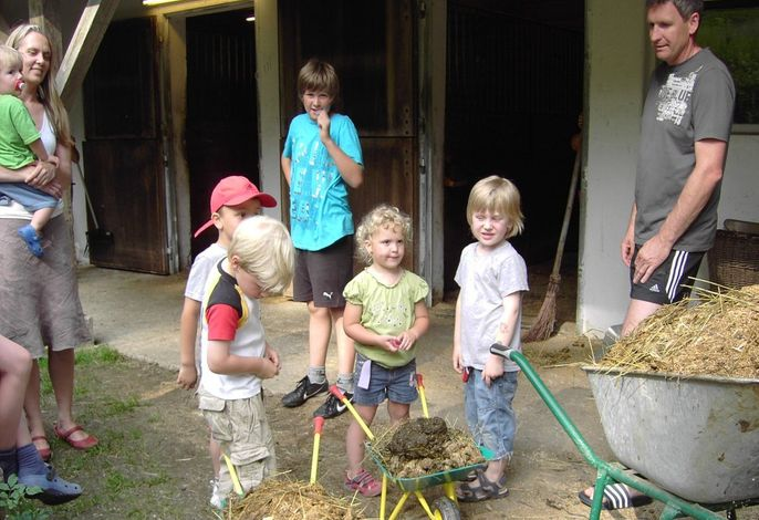Kinder bei der Stallarbeit