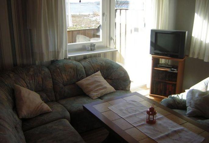 Wohnzimmer mit Wohnlandschaft und Fernseher mit Blick aus dem Fenster auf die Schlei