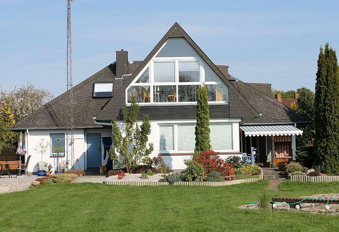 Außenansicht vom Ferienhaus mit Garten und Terrasse mit Strandkorb und kleinem Teich