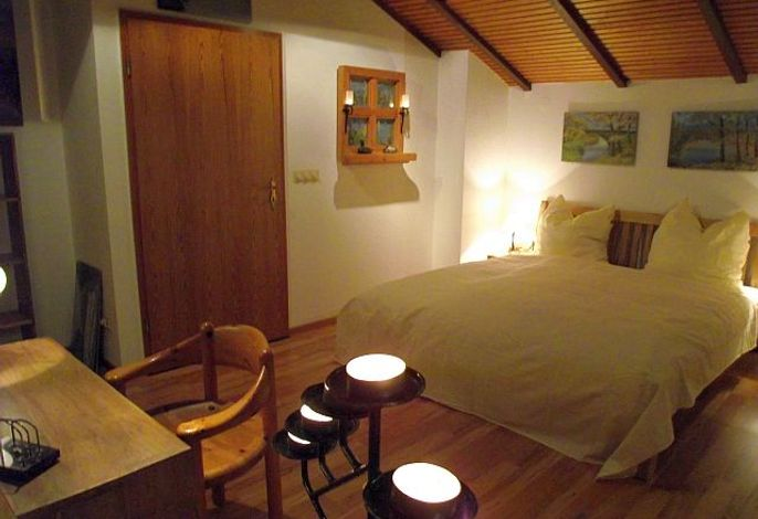 Schlafzimmer mit Doppelbett und Schreibtisch