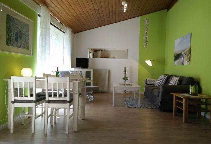Schick eingerichtetes Wohnzimmer mit grüner Tapete und grauen Möbeln