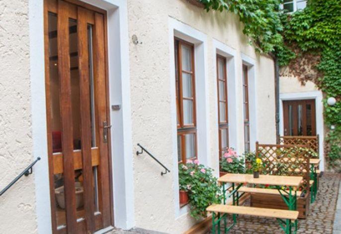 Sitzgelegenheit im Innenhof, Eingang zu Fewo 54qm
