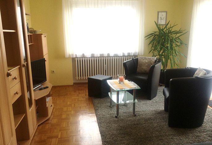 Wohnzimmer, Sitzgruppe, Schrankwand mit SAT-TV, Bücherauswahl