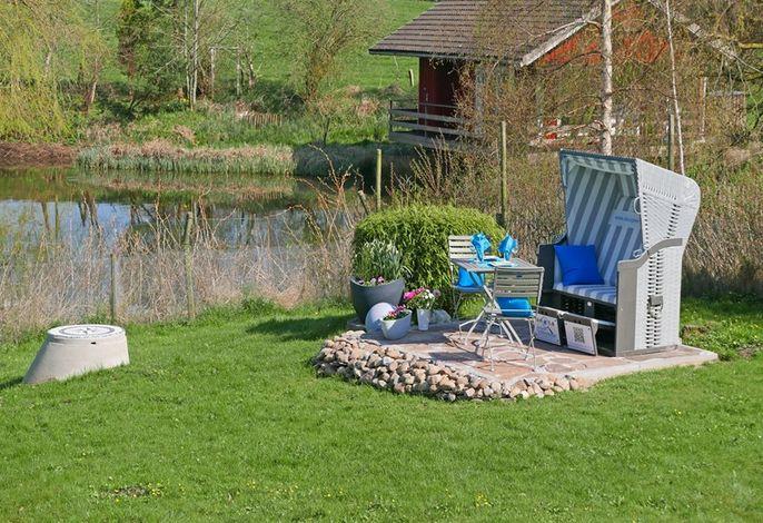 Ein eigener strandkorb auf der Terrasse am Teich
