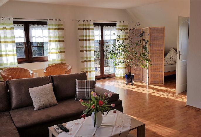 Wohnzimmer mit Couch und Balkontür