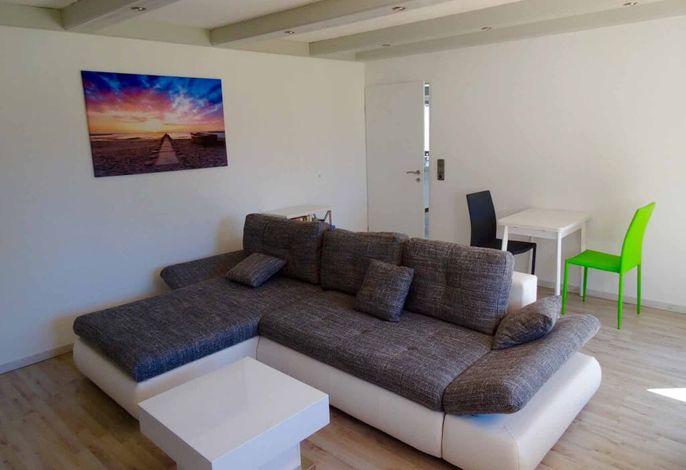 Wohnzimmer mit Schlafcouch und Essgruppe
