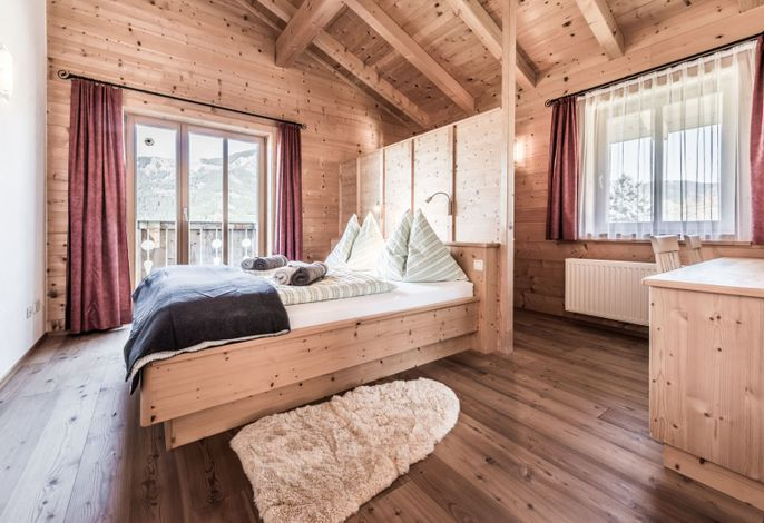 Gemütliches Schlafzimmer mit hochwertigem Bett, Schreibtisch und kuscheligem Schaffell.