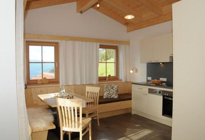 traumhafte Wohnküche mit Liegecouch und direkten Balkonzugang
