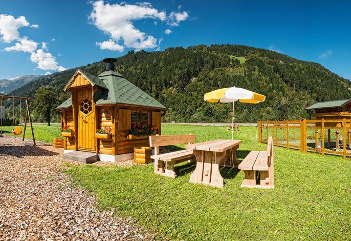 Außenansicht mit Spielplatz, Grillhütte und Tierpark